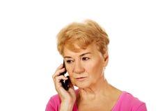 Bekymrad hög kvinna som talar till och med telefonen Royaltyfri Foto