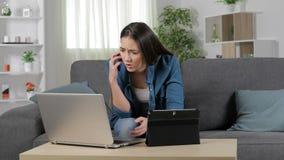 Bekymrad kvinna som använder åtskilliga apparater arkivfilmer