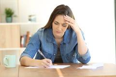 Bekymrad kvinna som hemma skrivar ett brev arkivfoto