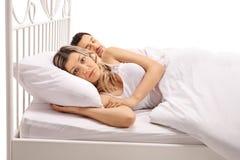 Bekymrad kvinna som ligger i säng med en grabb arkivbild