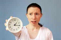 Bekymrad kvinna som pekar på klockatidledning arkivfoton