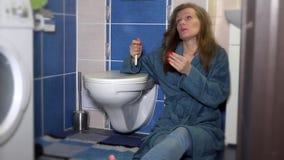 Bekymrad kvinna som ser en graviditetstest i badrummet lager videofilmer