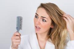 Bekymrad kvinna som ser hårkammen Royaltyfria Foton