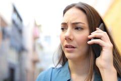 Bekymrad kvinna som talar på telefonen som går i gatan royaltyfri fotografi
