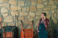 Bekymrad kvinnlig bonde som talar på mobiltelefonen royaltyfri fotografi