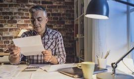 Bekymrad man som hemma kontrollerar hans inhemska räkningar royaltyfri fotografi