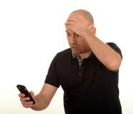 Bekymrad man som ser mobilen Arkivbild