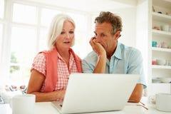 Bekymrad mitt åldrades par som ser bärbara datorn arkivfoton