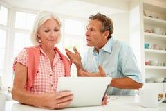 Bekymrad mitt åldrades par som ser den Digital minnestavlan Royaltyfri Fotografi