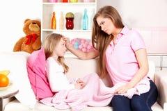 Bekymrad moder med det sjuka barnet royaltyfri foto