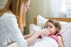 Bekymrad moder som dåligt ger medicin till henne ungen Royaltyfri Bild