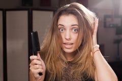 Bekymrad nätt flicka som trycker på flödande ovårdat hår royaltyfri foto