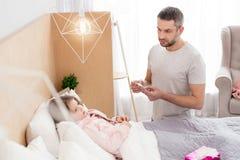 Bekymrad pappa som tar omsorg av hans sjuka dotter Royaltyfri Bild