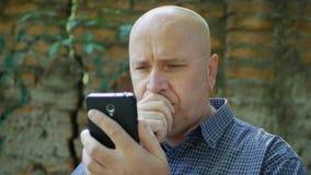 Bekymrad person som ser till hjälplös mobil text som är besviken och royaltyfria foton