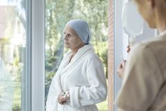 Bekymrad sjuk hög kvinna med cancer under behandling i ett sjukvårdhus royaltyfria foton