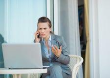 Bekymrad talande mobiltelefon för affärskvinna Royaltyfri Bild