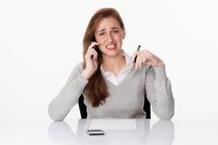 Bekymrad 20-talkvinna som kallar på telefonen på gles vit bakgrund Arkivfoto