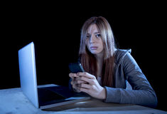 Bekymrad tonåring som använder mobiltelefonen och datoren, som internetcyberpennalismen förföljde det missbrukade offret Royaltyfri Foto