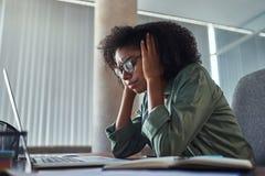 Bekymrad ung afrikansk affärskvinna på hennes arbetsplats arkivbilder