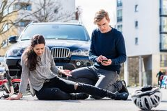 Bekymrad ung chaufför som kallar ambulansen, når att ha slågit den kvinnliga cyklisten fotografering för bildbyråer