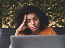 Bekymrad ung kvinna som ser bärbara datorn i kafé royaltyfri foto