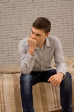 Bekymrad ung man som djupt sitter i tanke Arkivfoto