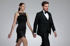 Bekymrad ung man som går, medan rymma hans flickväns hand arkivfoto