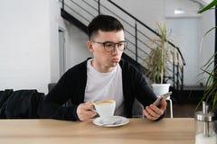 Bekymrad ung man som läser ett meddelande med dåligt meddelande på den moderna smartphonen som sitter i kafé Frustrerat och förar arkivbild