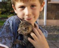 Bekymrad ung pojke med den älsklings- kattungen Arkivfoton