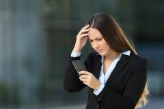 Bekymrad utövande läs- dåliga nyheter i en mobiltelefon royaltyfria bilder