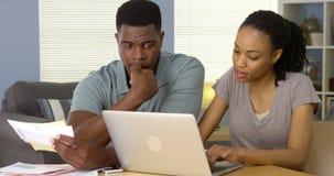 Bekymrade afrikansk amerikanpar som direktanslutet ser till och med räkningar royaltyfri bild
