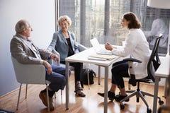 Bekymrade höga par som har konsultation med kvinnlig doktor In Hospital Office royaltyfri foto