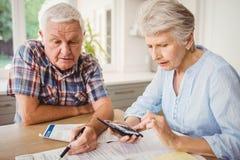 Bekymrade höga par som kontrollerar deras räkningar Royaltyfria Foton
