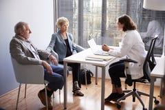 Bekymrade h?ga par som har konsultation med kvinnlig doktor In Hospital Office royaltyfri foto