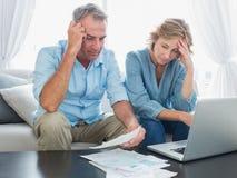Bekymrade par som direktanslutet betalar deras räkningar med bärbara datorn Fotografering för Bildbyråer