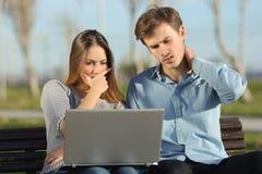 Bekymrade studenter eller entreprenörer som utomhus håller ögonen på en bärbar dator royaltyfria bilder