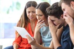 Bekymrade vänner som hemma kontrollerar minnestavlaonline-nyheterna royaltyfria bilder