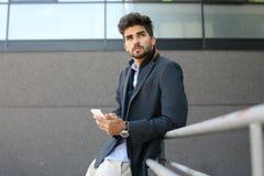 Bekymrat affärsmananseende och smart telefon för innehav royaltyfria foton