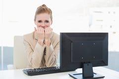 Bekymrat bita för affärskvinna spikar på skrivbordet i regeringsställning Arkivbilder