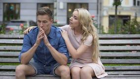 Bekymrat grabbsammanträde på bänken, flickvän som ner lugnar honom, problem, service arkivfilmer