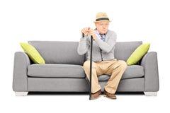 Bekymrat högt gentlemansammanträde på en soffa Royaltyfri Bild
