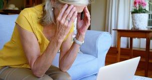 Bekymrat högt kvinnasammanträde på soffan hemmastadd 4k stock video