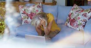 Bekymrat högt kvinnasammanträde på soffan 4k arkivfilmer