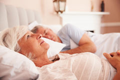 Bekymrat högt ligga för kvinna som är vaket i säng royaltyfri bild
