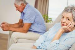 Bekymrat högt kvinnasammanträde på soffan Arkivbild