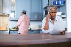 Bekymrat kvinnaläsningdokument, medan stå i kök fotografering för bildbyråer