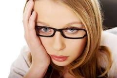 Bekymrat kvinnasammanträde för barn på skrivbordet Royaltyfri Foto