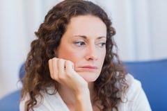 Bekymrat kvinnasammanträde på soffan royaltyfria bilder