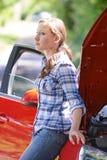 Bekymrat kvinnligt bilistanseende bredvid den brutna ner bilen arkivfoton