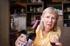 Bekymrat kvinnligt erbjudande vin och exponeringsglas royaltyfri bild
